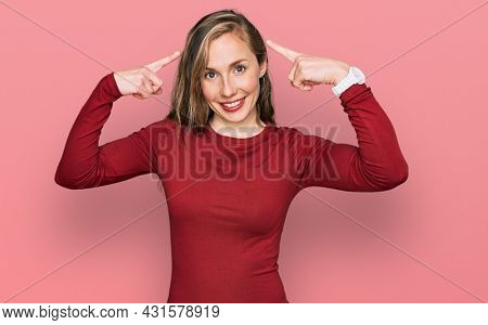 Young blonde woman wearing casual clothes smiling pointing to head with both hands finger, great idea or thought, good memory