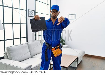 Young indian technician holding toolbox and screwdriver at house with angry face, negative sign showing dislike with thumbs down, rejection concept