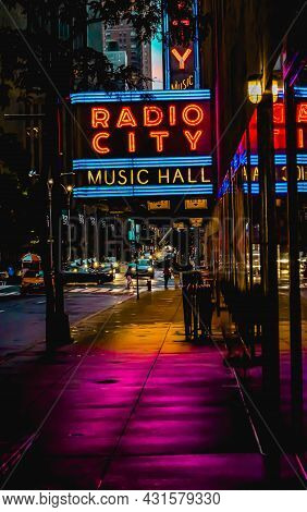 Radio City Music Hall Marquee Neon Sign Reflecting Off Building And Near Silhouette Tree Leaves And