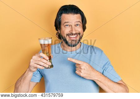 Middle age caucasian man drinking a pint of beer smiling happy pointing with hand and finger