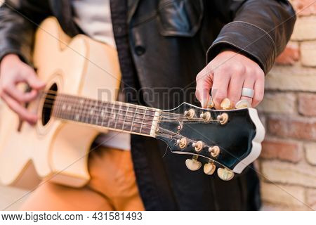Street musician close up tuning the guitar. Fingers turning the tuning pegs of an acoustic guitar