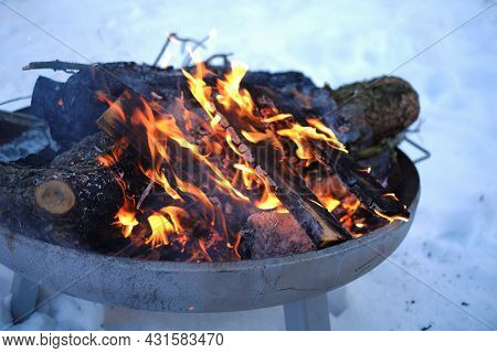 Burning Firewood In The Winter Snow Garden.burning Firewood Background.flames And Sparks