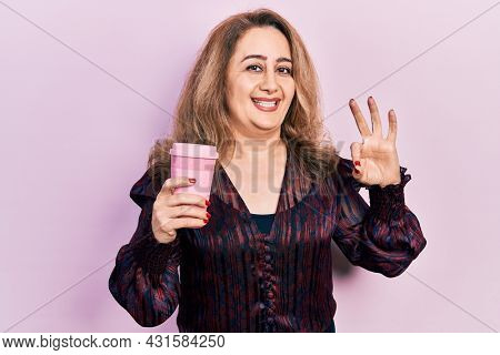 Middle age caucasian woman drinking a take away coffee doing ok sign with fingers, smiling friendly gesturing excellent symbol