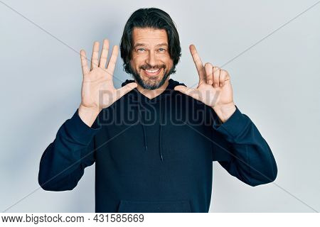 Middle age caucasian man wearing casual sweatshirt showing and pointing up with fingers number seven while smiling confident and happy.