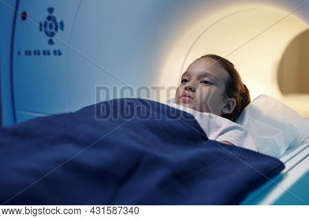 Calm little girl going to undergo mri scan examination while moving into machine