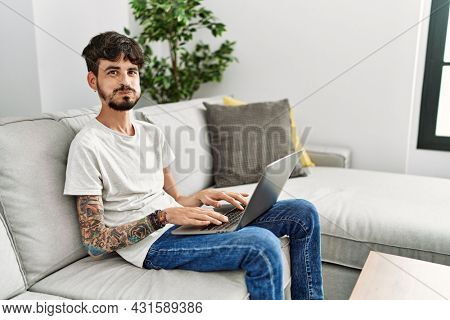 Hispanic man with beard sitting on the sofa puffing cheeks with funny face. mouth inflated with air, crazy expression.