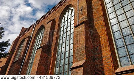 The Main Nave Of The Church In Gdansk With Tall Glass Windows And Brick Style Wall Seen From The Out