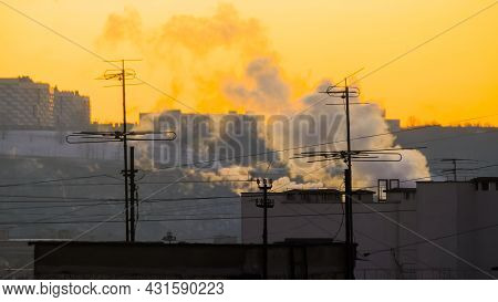 Roofs Of Old Apartment Buildings With Tv Antennas And White Smoke From Smokestack Against Morning Or