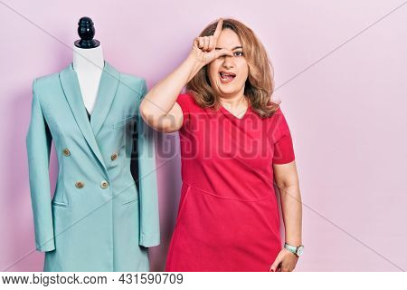 Middle age caucasian woman standing by manikin making fun of people with fingers on forehead doing loser gesture mocking and insulting.