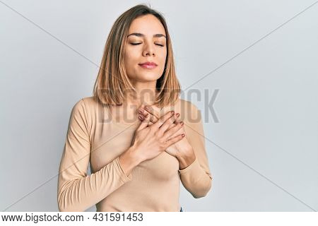 Young caucasian blonde woman wearing casual sweater smiling with hands on chest, eyes closed with grateful gesture on face. health concept.