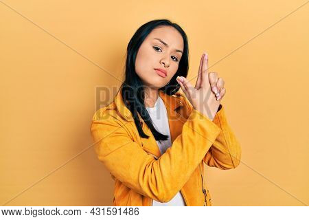 Beautiful hispanic woman with nose piercing wearing yellow leather jacket holding symbolic gun with hand gesture, playing killing shooting weapons, angry face