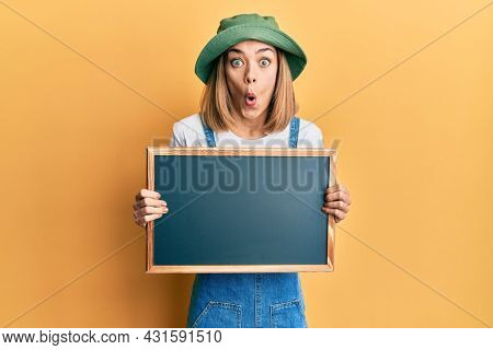 Young caucasian blonde woman holding blackboard afraid and shocked with surprise and amazed expression, fear and excited face.