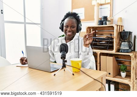 Young african woman working at radio studio smiling happy pointing with hand and finger to the side