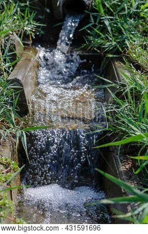 The Water Flows Through A Narrow Channel Among Green Grasses. A Rocky Channel With A Fast Water Flow