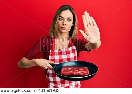 Young caucasian blonde woman wearing cook apron cooking meat on pan with open hand doing stop sign with serious and confident expression, defense gesture