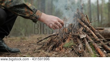 Low angle shot of a man is trying make a fire in the forest. Close-up of a man's hand lighting a campfire. Lighting a fire in the forest by a person. Low angle of a burning fire made of brushwood.