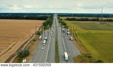 Aerial view of a motorway in summer on a cloudy day. Aerial view of a suburb road with trucks. Drone  above a highway with driving cars.