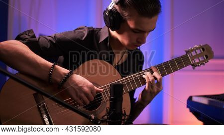 Musician in a headphones records his composition in a music Studio using professional audio microphone. Man plays guitar. Young man plays a musical instrument.