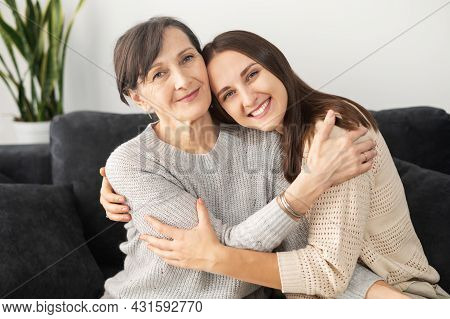 A Portrait Of A Senior Mother And An Adult Daughter Sitting On The Comfortable Couch, A Mom And A Da