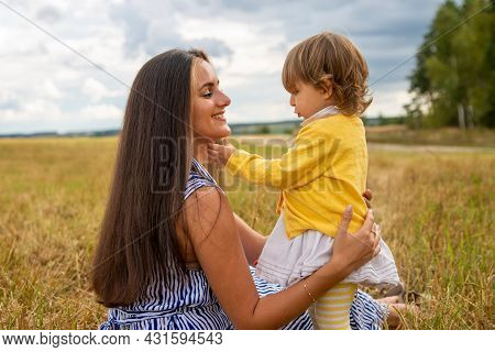 Happy Child And His Mom Have Fun Outdoors In A Field Flooded With . Mom Holds The Child In Her Arms,