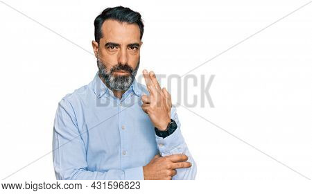 Middle aged man with beard wearing business shirt holding symbolic gun with hand gesture, playing killing shooting weapons, angry face