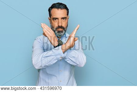 Middle aged man with beard wearing business shirt rejection expression crossing arms doing negative sign, angry face