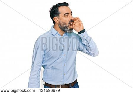 Middle aged man with beard wearing business shirt shouting and screaming loud to side with hand on mouth. communication concept.