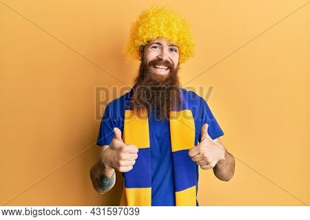 Redhead man with long beard football hooligan cheering game wearing funny wig success sign doing positive gesture with hand, thumbs up smiling and happy. cheerful expression and winner gesture.