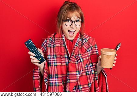 Redhead young woman wrapped in a red warm red blanket eating icecream and watching tv celebrating crazy and amazed for success with open eyes screaming excited.