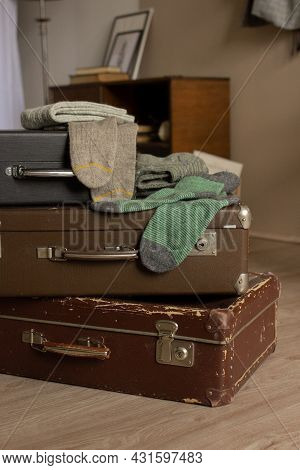 Many Knitted Woolen Socks Lying In Old Suitcases