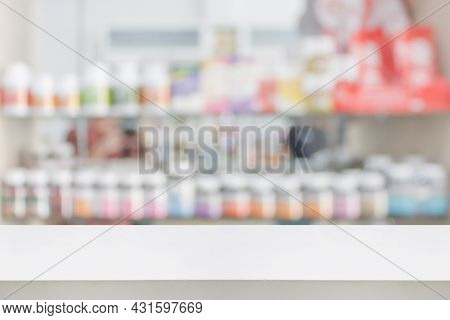 Pharmacy Store Counter Table Top With Blur Medicine On Shelves In The Drugstore Background