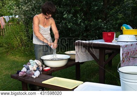 Woman Washes Clothes With Her Hands In Old Basin, Rinses And Then Wrings Out The Washed Laundry Outd