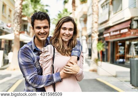Young hispanic couple hugging in love at the city. Girlfriend and boyfriend together in love walking on the street