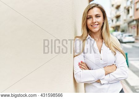 Beautiful blonde woman smiling happy leaning on the wall outdoors on a sunny day
