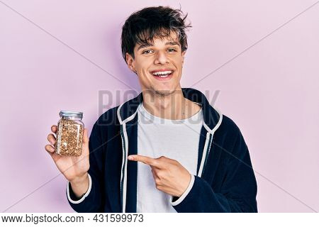 Handsome hipster young man holding lentils bowl smiling happy pointing with hand and finger