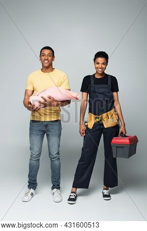 African American Father Holding Baby Covered In Blanket Near Repairwoman With Toolbox On Grey