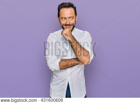 Middle age man wearing casual clothes with hand on chin thinking about question, pensive expression. smiling with thoughtful face. doubt concept.