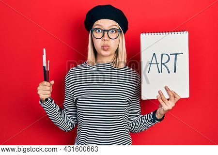 Beautiful blonde woman holding art notebook and brushes puffing cheeks with funny face. mouth inflated with air, catching air.