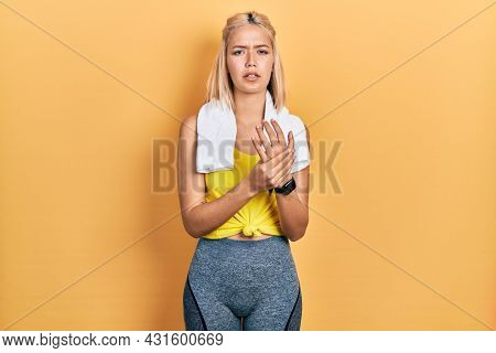 Beautiful blonde sports woman wearing workout outfit suffering pain on hands and fingers, arthritis inflammation