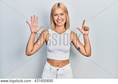 Beautiful blonde woman wearing casual style with sleeveless shirt showing and pointing up with fingers number seven while smiling confident and happy.