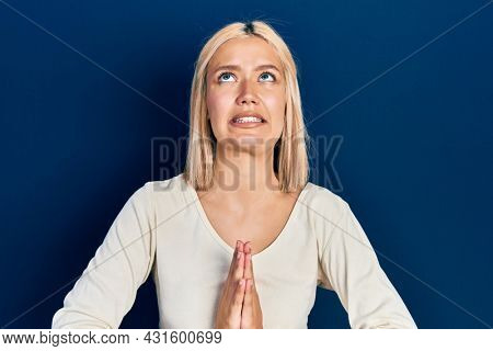Beautiful blonde woman wearing casual sweater begging and praying with hands together with hope expression on face very emotional and worried. begging.