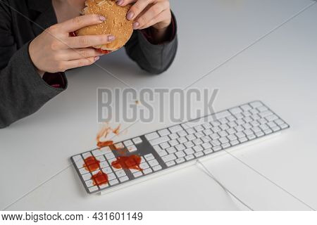 A Faceless Woman Is Eating A Burger And Dripping Ketchup On The Keyboard