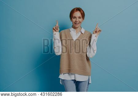 Happy Stylish Red-haired Woman In Casual Outfit Showing Up With Forefingers At Copy Space And Smilin