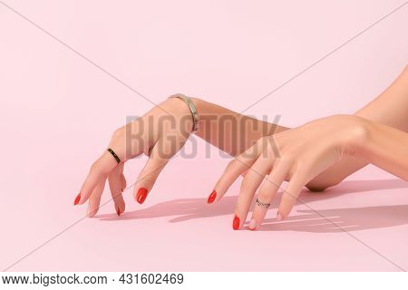 Womans Hands With Red Manicure On Pink Background. Manicure Design Trends