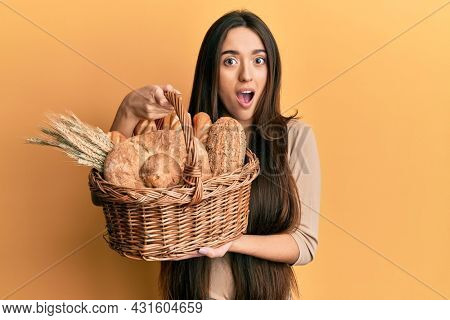 Young hispanic girl holding wicker basket with bread afraid and shocked with surprise and amazed expression, fear and excited face.