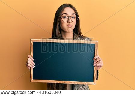 Young hispanic girl holding blackboard puffing cheeks with funny face. mouth inflated with air, catching air.