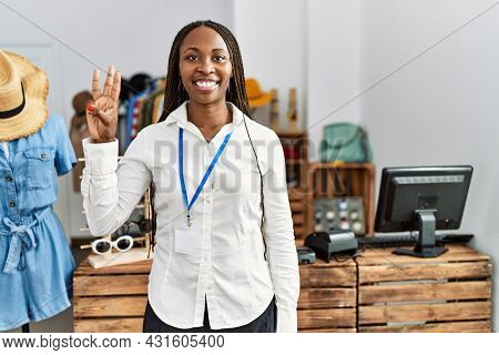 Black woman with braids working as manager at retail boutique showing and pointing up with fingers number three while smiling confident and happy.