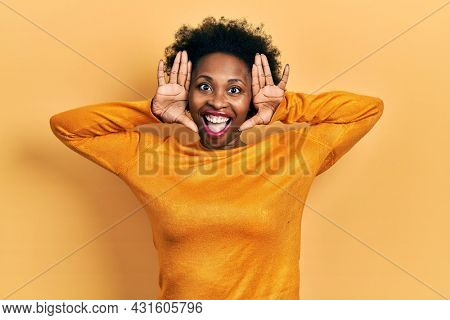 Young african american woman wearing casual clothes smiling cheerful playing peek a boo with hands showing face. surprised and exited