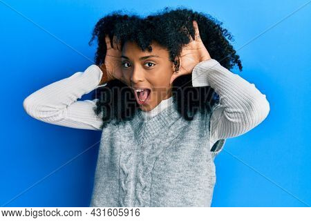 African american woman with afro hair wearing casual winter sweater smiling cheerful playing peek a boo with hands showing face. surprised and exited