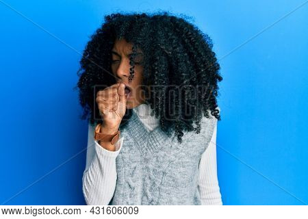 African american woman with afro hair wearing casual winter sweater feeling unwell and coughing as symptom for cold or bronchitis. health care concept.